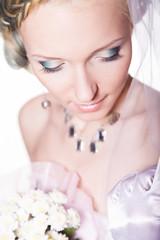 Невеста смотрит вниз с букетом, фото в студии