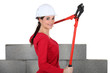 Woman holding bolt-cutters by unfinished wall
