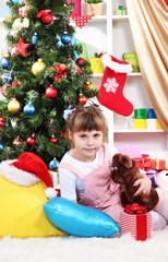 Little girl sitting near the Christmas tree in  festively