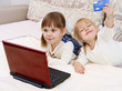Two little girls are with a laptop and a credit card