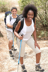mixed couple rambling through nature with walking pole
