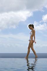 Woman walking along an infinity pool
