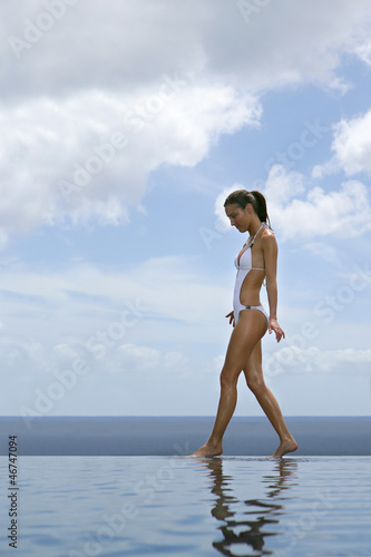 Woman walking along an infinity pool