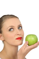 Woman in red lipstick holding a green apple