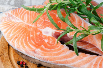 Close up salmon stake with rosemary on wooden board