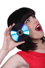 a woman sticking a cd near her ear