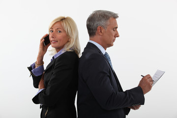 mature businessman and female partner standing back to back