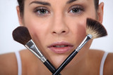 Closeup of a woman with makeup brushes