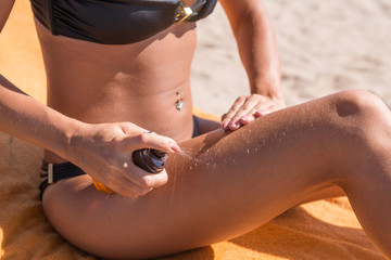 Sensous slim woman applying suntan oil