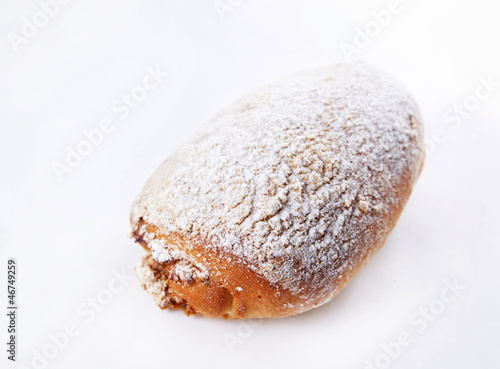 Baked bun dusted with powdered sugar