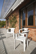 Three plastic chairs in a sunny terrace