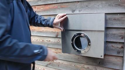 Mann wirft Brief in Briefkasten