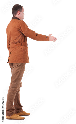 back view of businessman in  movement reaches out to shake hands