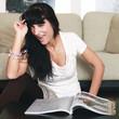 Hübsche junge Frau liest eine Zeitschrift