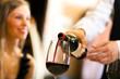 Waiter serving red wine
