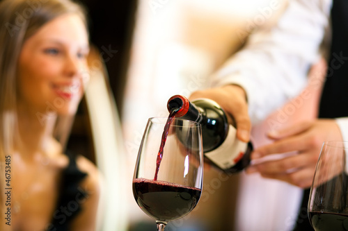 Waiter serving red wine
