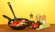 frying pan with vegetables on yellow background