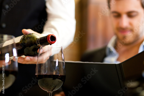 Kelner serwuje czerwone wino