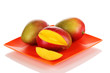 Ripe appetizing mango on red plate isolated on white