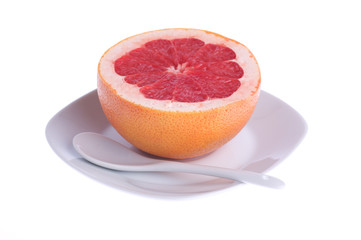 red grapefruit on a plate on a white background