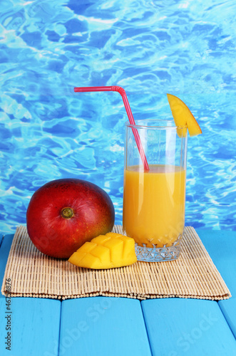 Ripe appetizing mango on woven napkin on water background