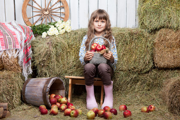 Portrait of girl villager with  basket of apples in hayloft