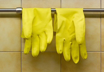 Yellow Rubber Gloves Against Kitchen's Wall