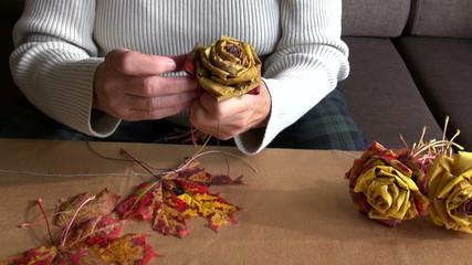 grandmother hands make original flower from maple leaves