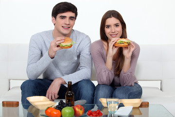 Young couple eating hamburgers
