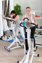 Women using stepper machine in gym