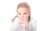 young blond girl drinks water from a glass