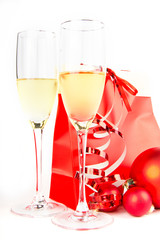 two glass goblets with champagne and present on white background
