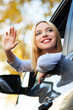 Woman waving from car window