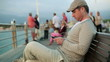 Happy young man using smartphone on pier, steadicam shot