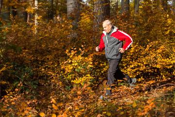 Senior joggt im Herbstwald