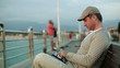 Young man with tablet computer on pier, steadicam shot