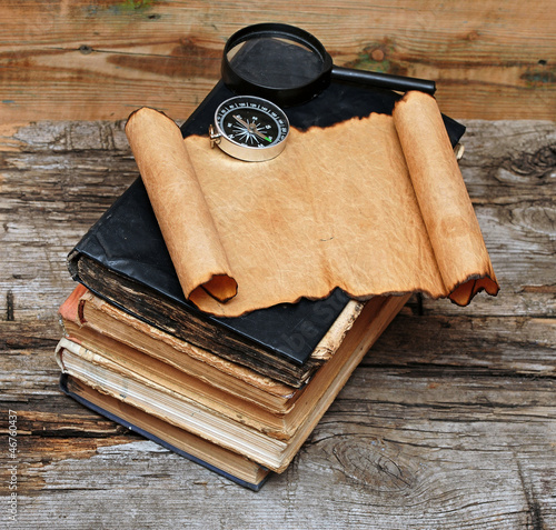 Stack of antique books with compass, magnifying glass and paper