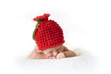 cute newborn baby in a red berry cap on white background
