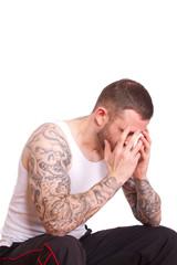 tätowierter Mann mit Kopfschmerzen