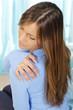 Frau hält Hand auf Schulter bei Verspannungen