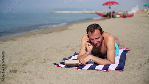 Man relaxing on the beach and talking on a cell phone