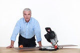 Grey-haired man with circular saw