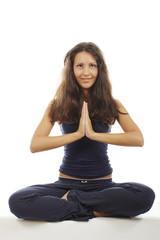 Hübsche Frau im Yogasitz mit gefalteten Händen