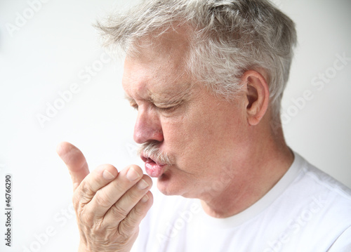 senior man sneezing into his hand