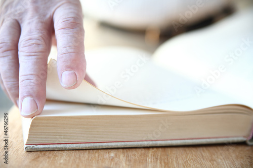 a man turns the pages of a large book