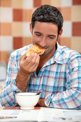 Smiling man eating croissant for breakfast with a magazine