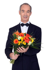 senior man in a suit holding flowers
