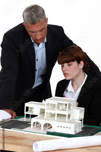 Architect and assistant looking at model house