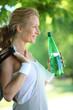 A smiling sportswoman holding a bottle.