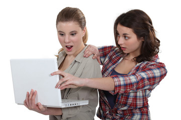 Two shocked girls looking at laptop